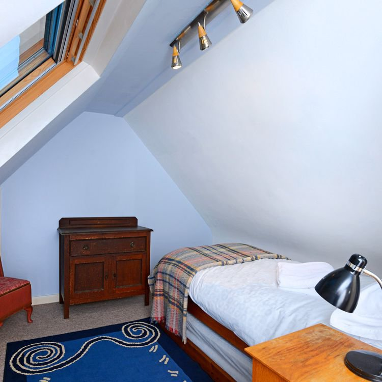 The attic room, reached through the single upstairs bedroom, can have twin beds.