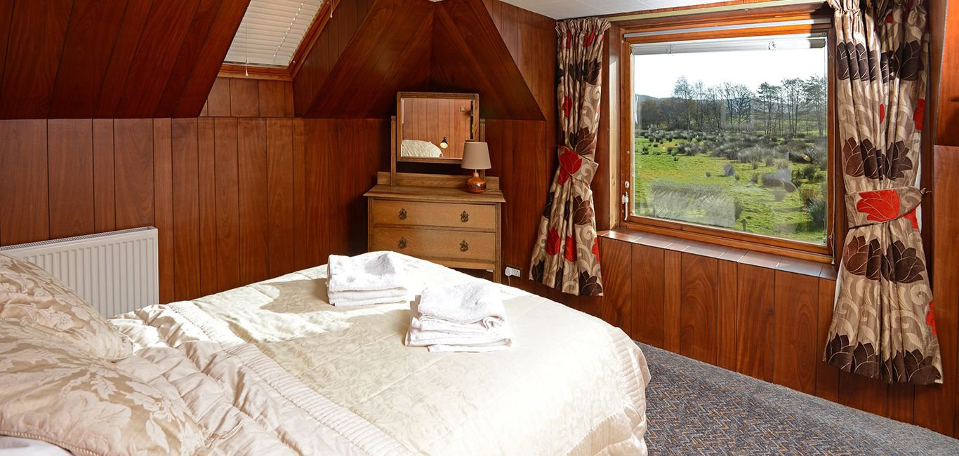 The double bedroom looks out over fields and trees.