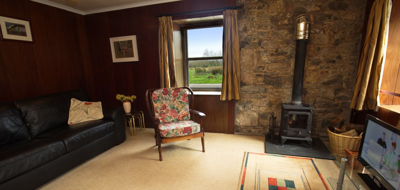 The holiday cottage has a cozy sitting room with wood-burning stove.