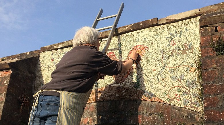 Helen Miles replacing missing tiles in the garden mosaic at Kirkennan